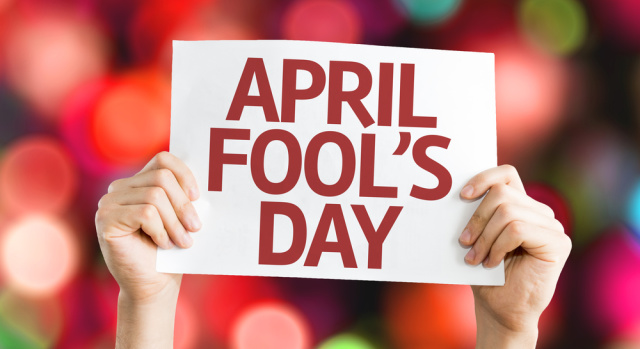 Pair of hands holding up a notice with 1st April, April Fool's Day
